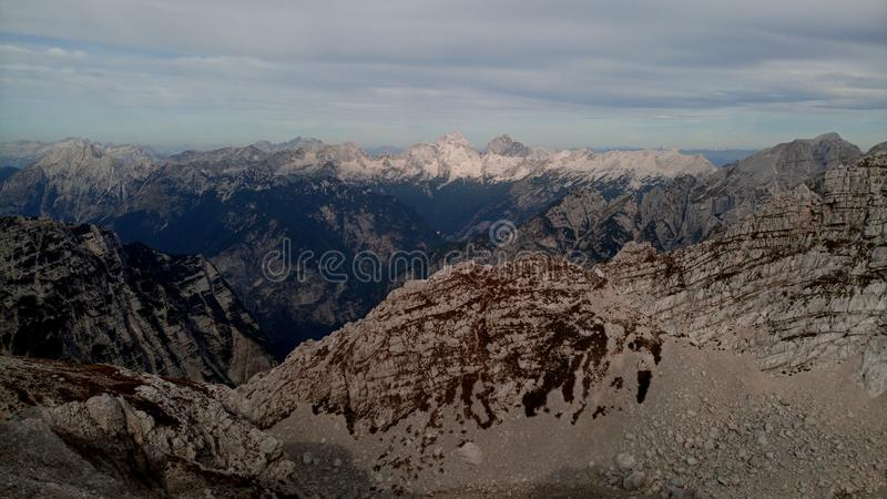 View on the Slovenian alps. Clear is blue with clouds. Under the mountain is deep valley with forests. Mountains are beautifuly white. Some of he hills is royalty free stock images