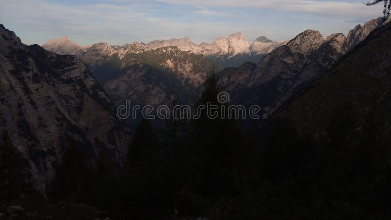 View on the Slovenian Alps. Mountains are lighted by raising sun. Valleys are deep woth forests. Sky is little cloudy. Tops of the peaks are just white rock royalty free stock images