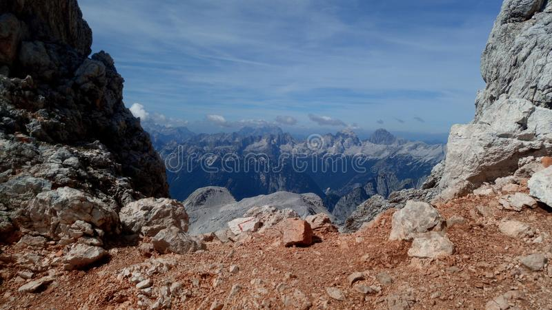 View on the Slovenian alps. From the saddle under thr Triglav peak. Photo is framed by the rocky walls. Clear is blue with clouds royalty free stock photo