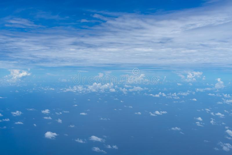 View of small abstract white cloud with bright blue sky horizon and vast sea ocean background from above flying airplane window stock photos