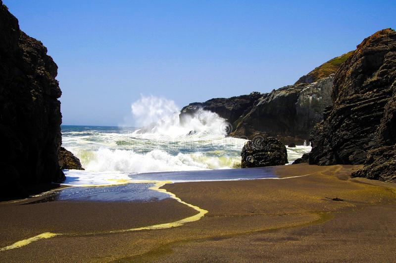 View on small bay with black volcanic lava sand foaming and splashing white waves stock photo
