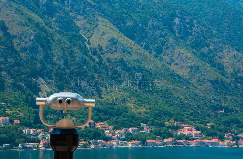 View of the small European city by the mountains and the sea through coin binocular. Kotor, Montenegro. Beautiful view of the mountains, the sea, and a small stock photography