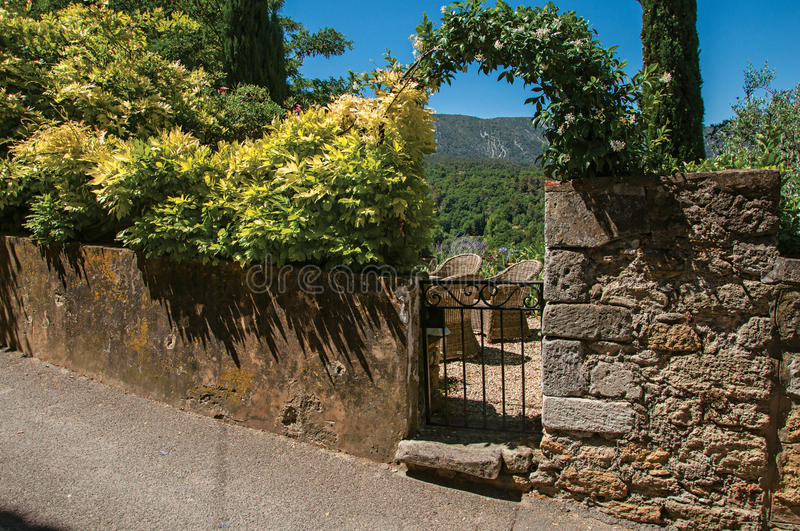 View of small garden behind iron gate and stone wall in the village of Ménerbes. stock photos