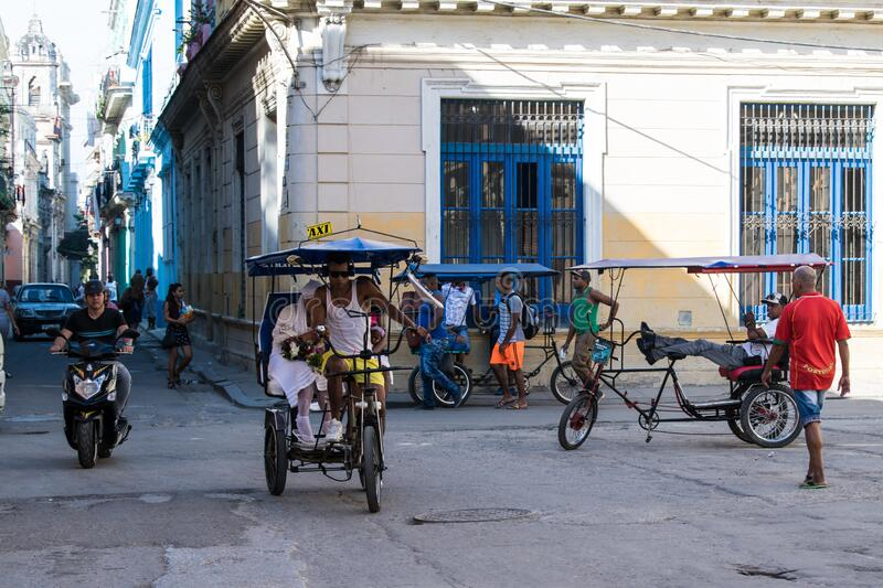 Havana, Street life with velotaxis, pedcabs and view to colonial buildings, in small street, Cuba royalty free stock photography