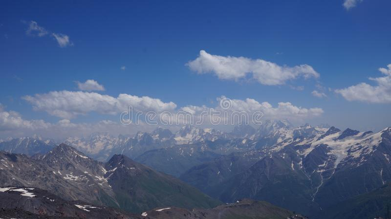 View of the snow-capped mountain peaks under a blue cloudy sky. View of the mountain snow-capped peaks of the Caucasus under a blue cloudy sky in summer royalty free stock photography