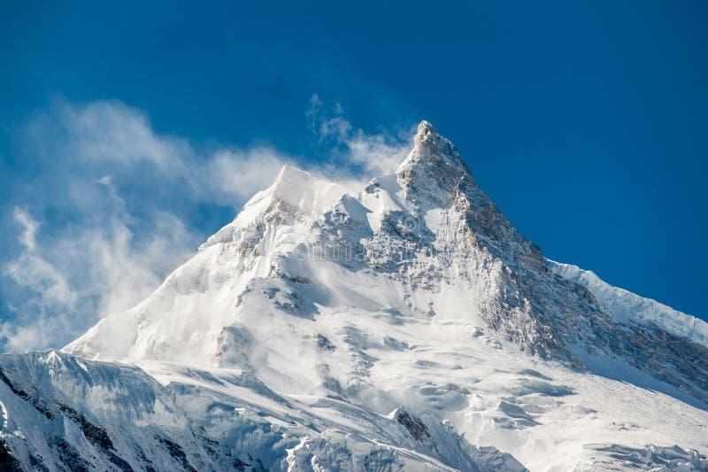 View of snow covered peak of Mount Manaslu 8 156 meters with clouds in Himalayas, Detail of snowy peak. stock photos
