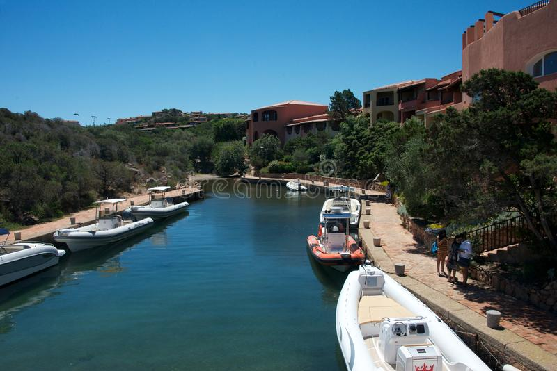 Boats moored in Porto Cervo`s marina between plants and luxury buildings royalty free stock images