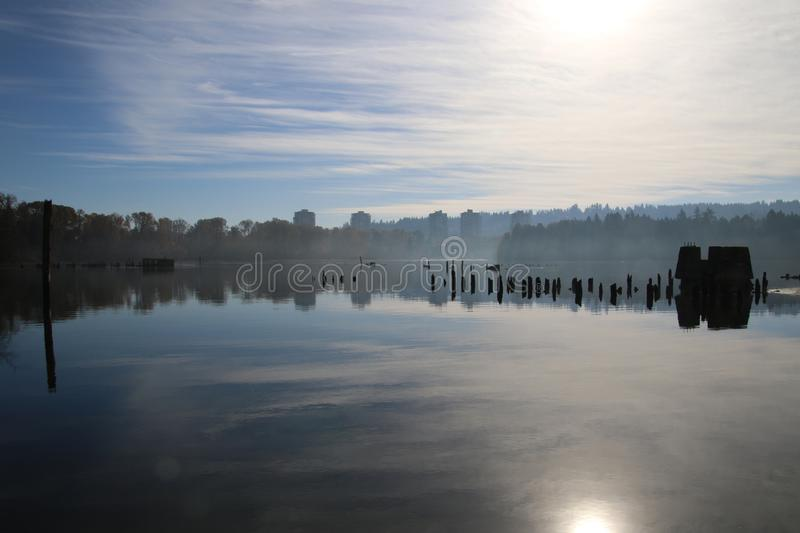 A view of some skyscrapers in the distance. With a calm body of water in the foreground .  There are derelict pilings on the right all under a blue cloudy sky stock images