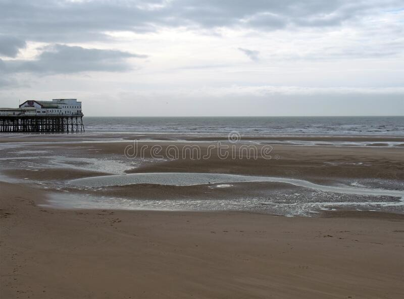 View of the south pier in blackpool with the beach at low tide in front of the sea and a cloudy sky royalty free stock image