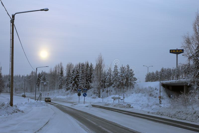 View of Southern Kuopio, Finland during a Cold Winter Day. Kuopio, Finland during winter. In this photo you can see cloudy sky, sun, road, Ikea sign, plenty of stock images