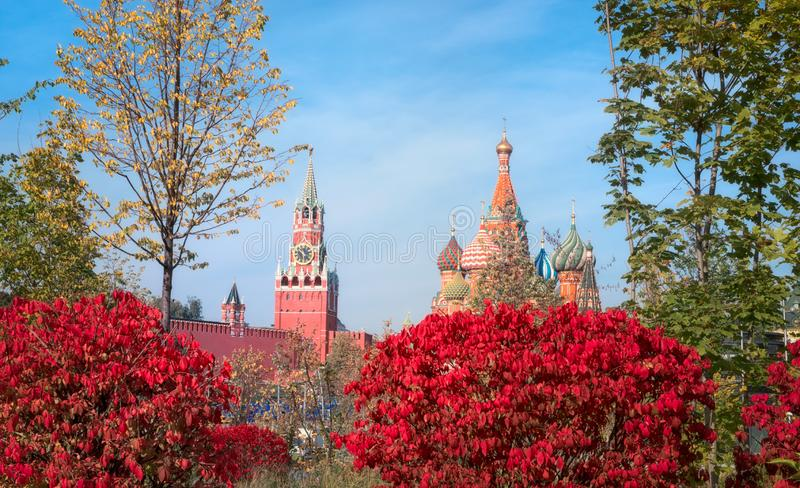 View of the Spasskaya Tower, the Moscow Kremlin and St. Basil`s Cathedral from autumnal Zaryadie park. Architecture and sights of stock photography