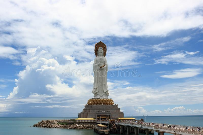 View from the square of Light on the bridge and statue of the three-faced Goddess of Mercy Guanyin against the background of sky stock photography