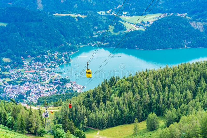 View of St.Gilgen, Wolfgangsee lake, mountains and colorful Seilbahn cable car gondolas from Zwolferhorn mountain. View of St.Gilgen village, Wolfgangsee lake royalty free stock photos