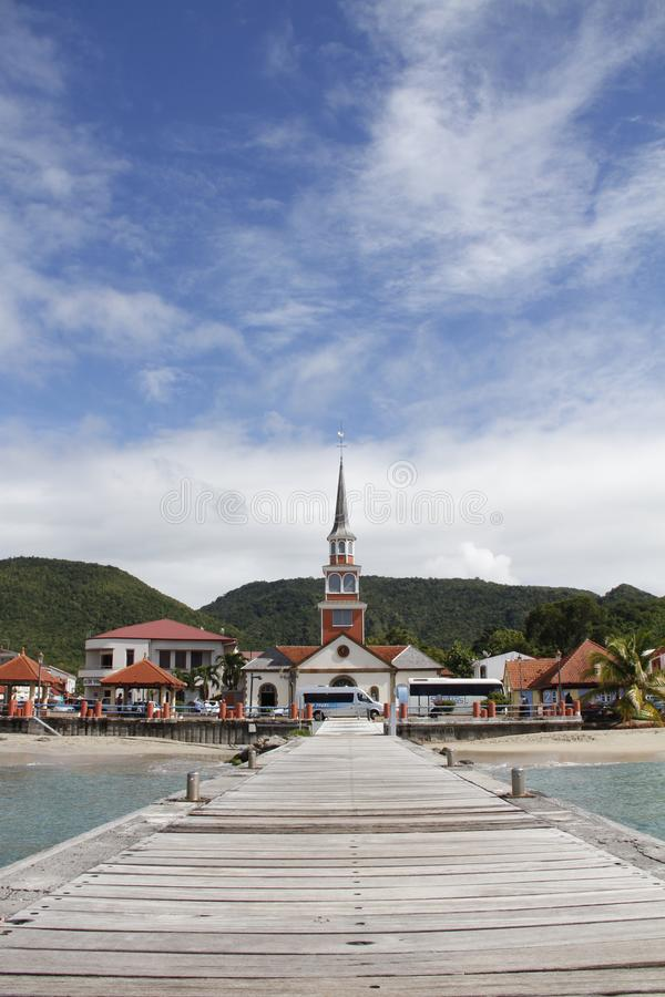 View of St. Henry church and Les Anses d`Arlet village from pier, Grand Anse, Martinique stock photography