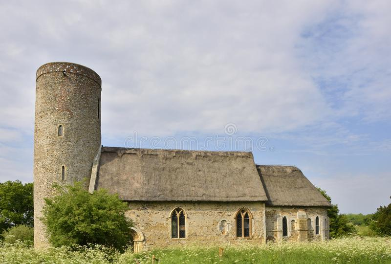 Historic English Round Tower Church. View of St Margaret`s, Hales, an historic English church with thatched roof and round tower, Norfolk, England royalty free stock image