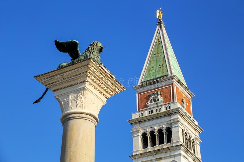 View of St Mark`s Campanile and Lion of Venice statue at Piazzetta San Marco in Venice, Italy. Campanile is one of the most recognizable symbols of the city royalty free stock photos
