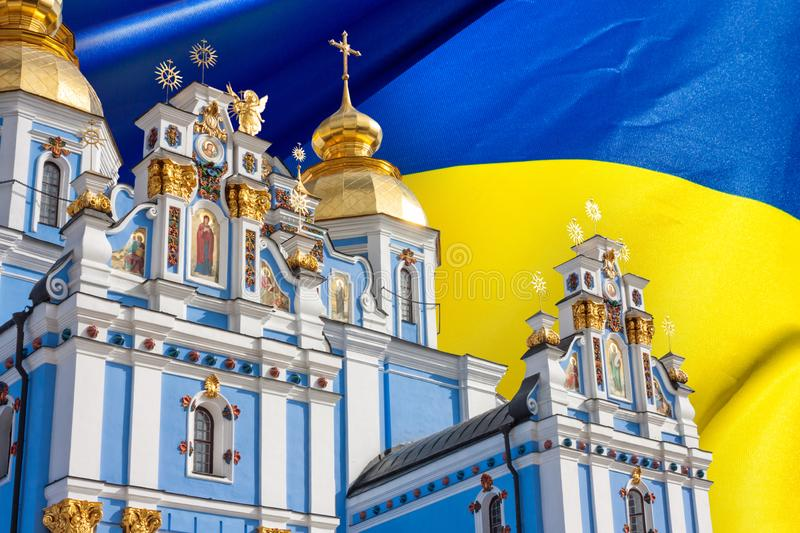 View of the St. Michaels Golden-Domed Monastery in Kiev, the Ukrainian Orthodox Church - Kiev Patriarchate, in the background flag stock photo