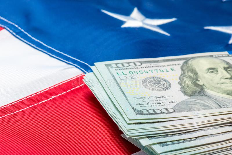 View of a stack of money lying on the flag of the United States of America. Close-up stock photos