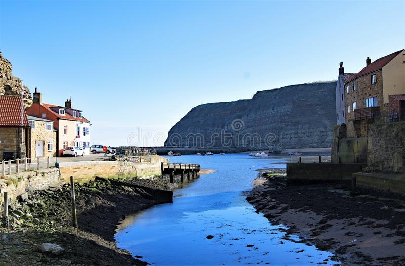 View of Staithes harbour and Penny Nab, near Scarborough, in North Yorkshire. royalty free stock image