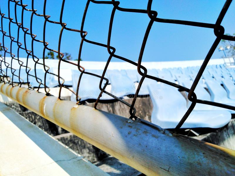 The view of the steel cage beside the chair on the grandstand. View steel cage chair grandstand royalty free stock images