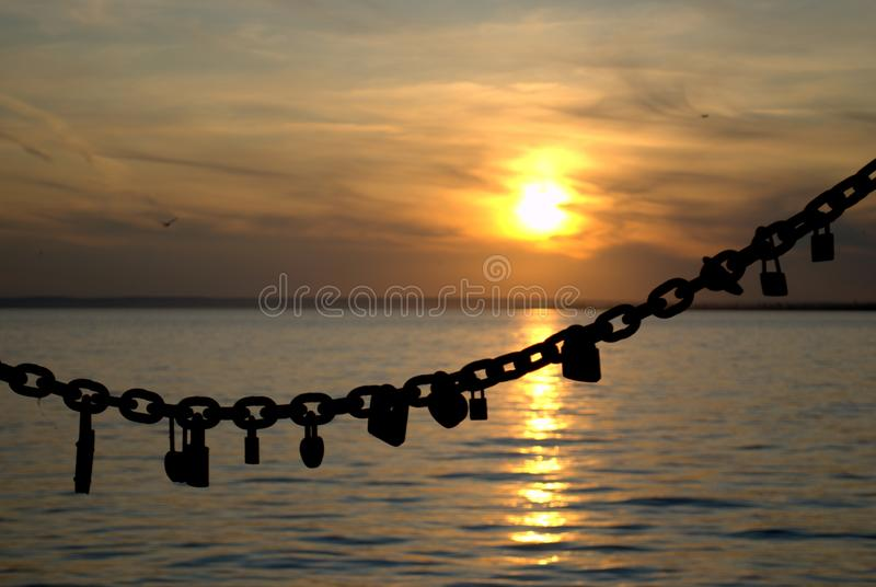 View of the steel chain of the fence of the embankment with locks hanging on it against the sunset sky. View of the steel chain of the fence of the embankment royalty free stock photos