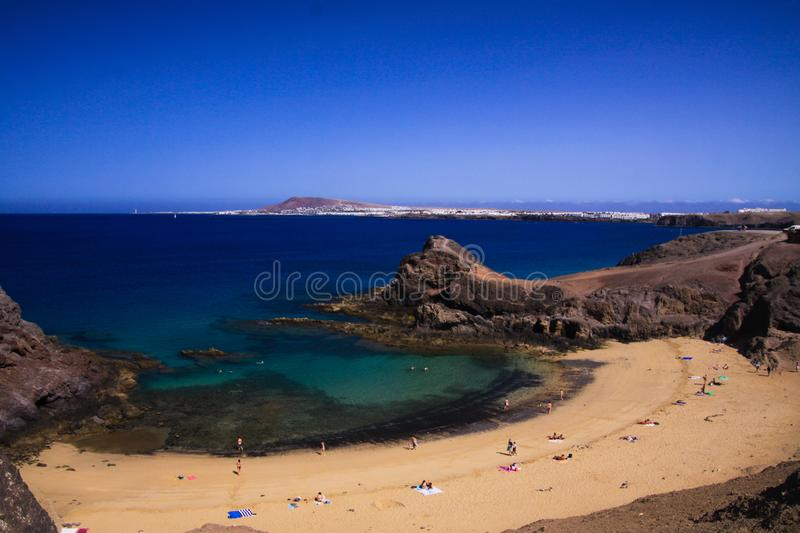 View from steep cliff into blue lagoon beach - Playa Papagayo, Playa Blanca - Lanzarote. View from steep cliff into blue lagoon beach royalty free stock images