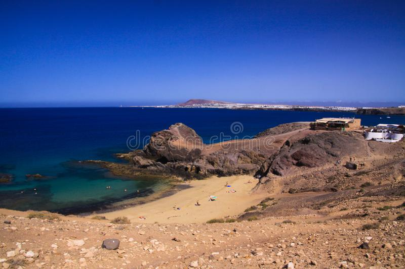 View from steep cliff into blue lagoon beach - Playa Papagayo, Playa Blanca - Lanzarote. View from steep cliff into blue lagoon beach - Playa Papagayo stock image