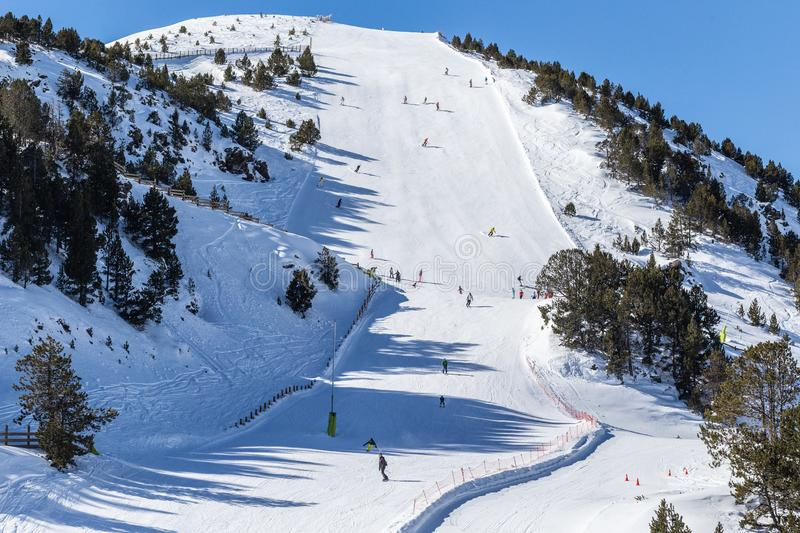 View of a steep ski slope at a winter resort in the Pyrenees, Andorra. Sunny winter day, a lot of snow, small figures of downhill athletes in the distance royalty free stock photography