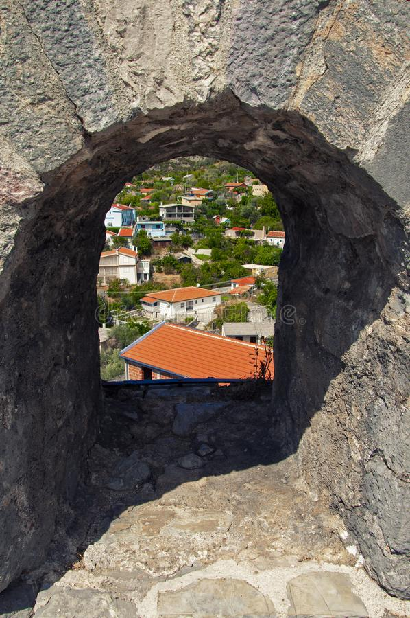 View through a stone arch with a fortress. White houses with red roofs, mountains covered with greenery. Old Bar in Montenegro. Top view through a stone arch royalty free stock photos