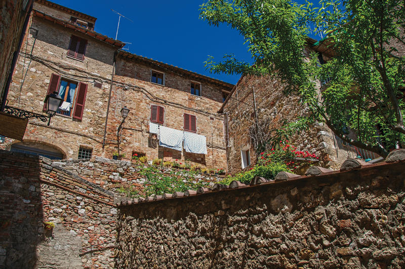 View of stone wall, old buildings with flowering plants at Colle di Val d`Elsa. stock photos