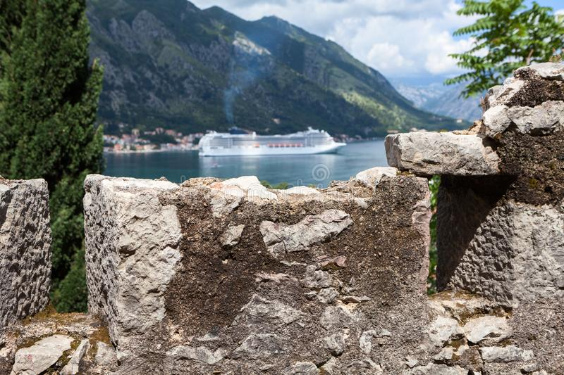 View at stone walls of ancient fortress with cruise ferryboat on the Gulf of Kotor. The Kotor city at summer season, Montenegro, royalty free stock images