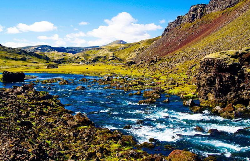View on stony scenic river creek through small green valley. Iceland stock photo