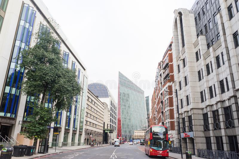 View of a street, buildings and typical red bus in London, England stock photography