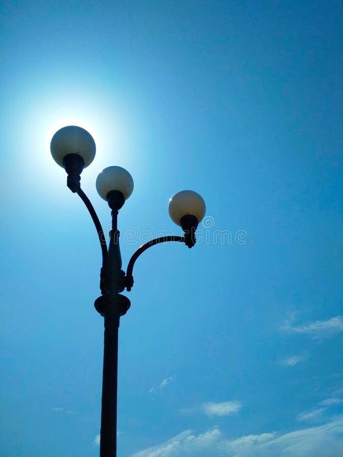 Street light, architectural decision. View of a street light against the background of the blue cloudless sky and shining sun stock photos