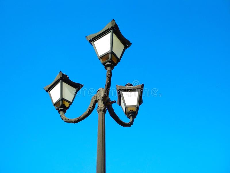 Street light, architectural decision. View of a street light against the background of the blue cloudless sky stock images