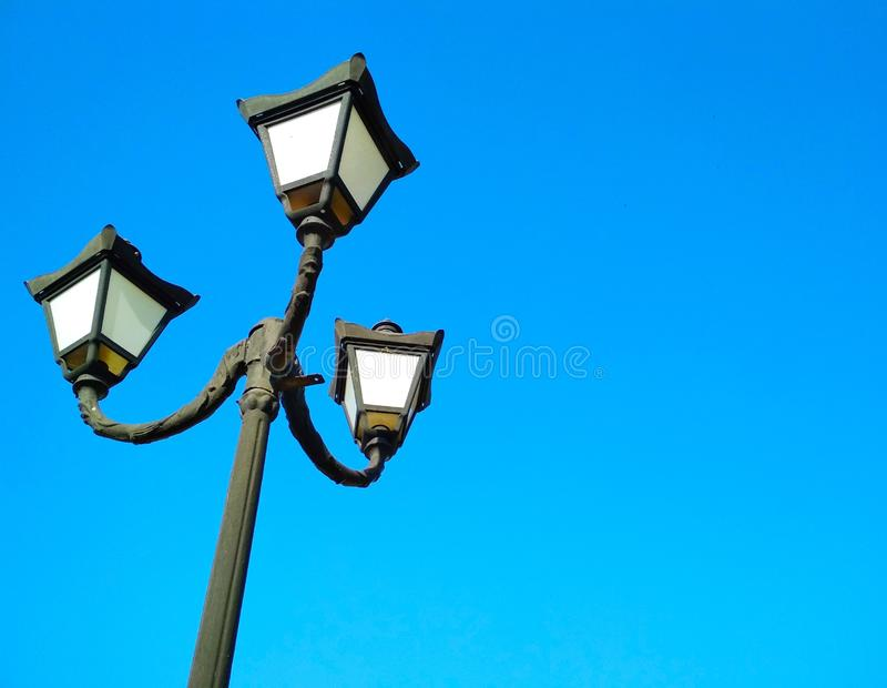 Street light, architectural decision. View of a street light against the background of the blue cloudless sky royalty free stock image