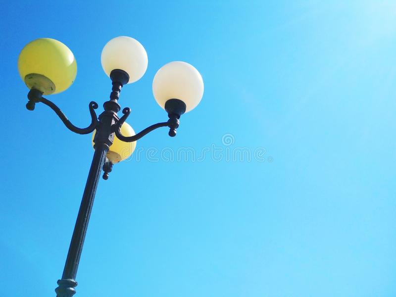 Street light, architectural decision. View of a street light against the background of the blue cloudless sky stock photography