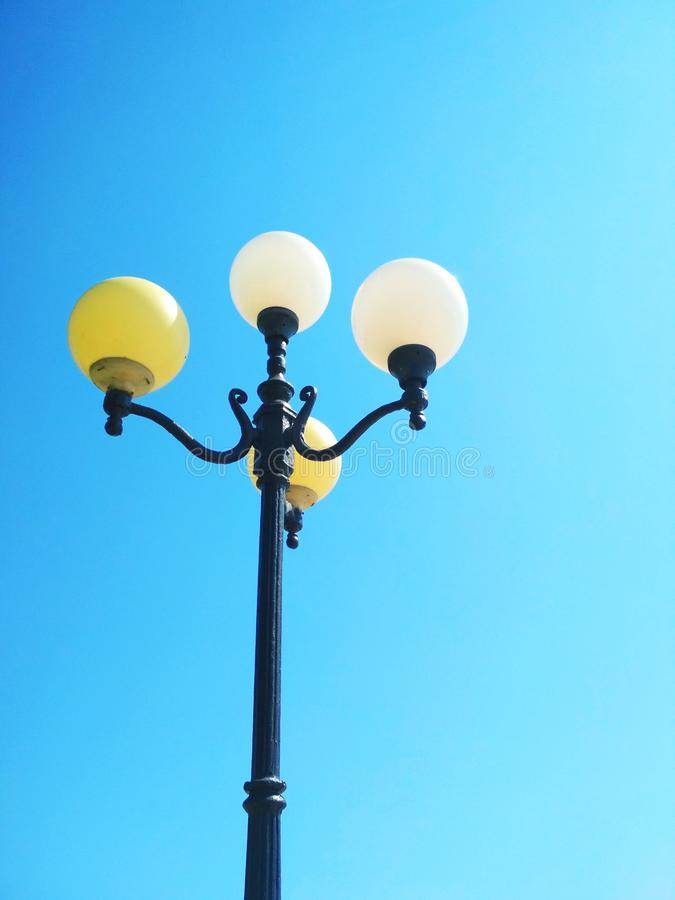 Street light, architectural decision. View of a street light against the background of the blue cloudless sky royalty free stock photo