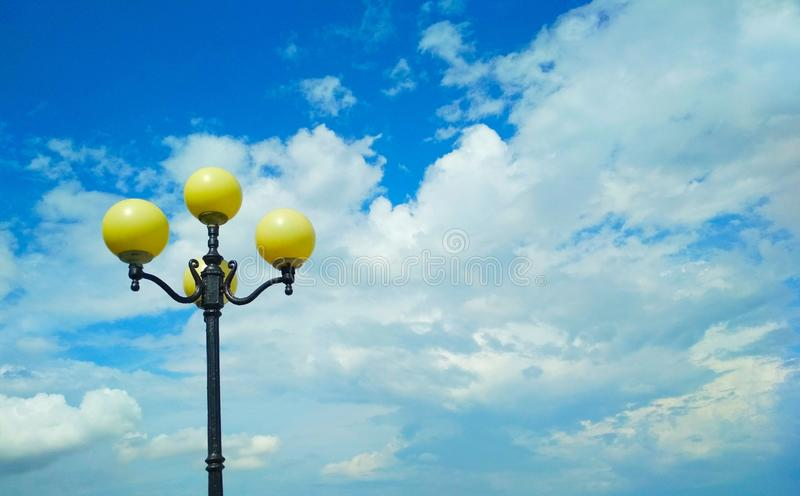 Street light, architectural decision. View of a street light against the background of the blue cloudy sky stock images