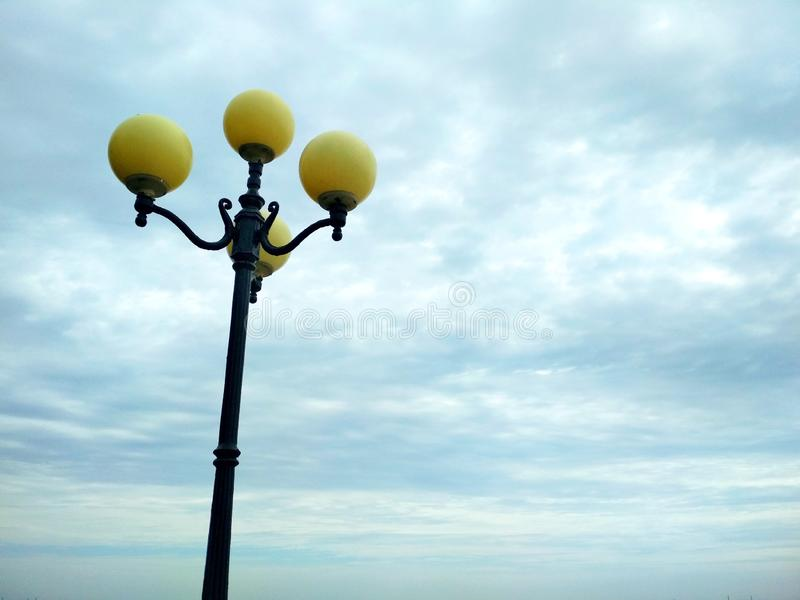 Street light, architectural decision. View of a street light against the background of the sky covered with clouds stock photos