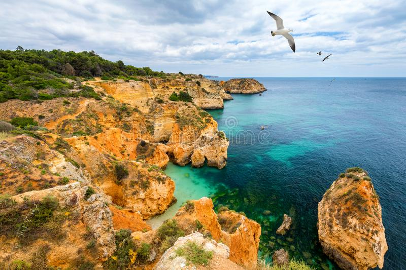 View of stunning beach with golden color rocks in Alvor town , Algarve, Portugal. View of cliff rocks on Alvor beach, Algarve royalty free stock photography