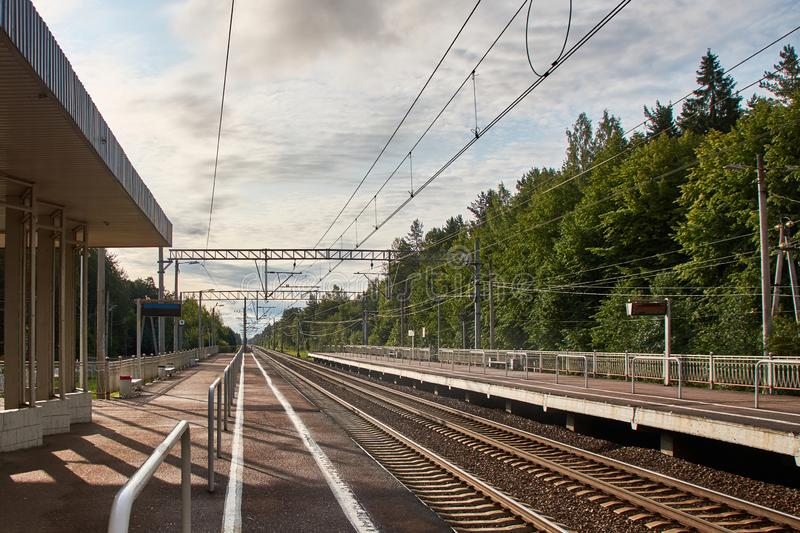 View of the suburban railway station with rails and platforms in two directions. Forest in the background stock photos