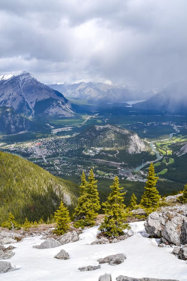 View From Sulphur Mountain. Snow covered mountain side with scattered pine trees in front of the view towards the snow capped rocky mountains, forest and town of stock photography