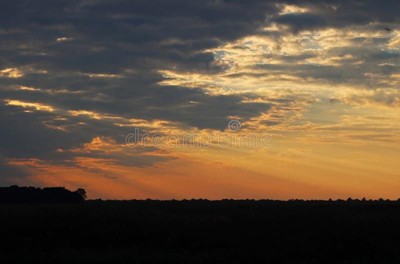 GLOWING SUNSET OVER AFRICAN BUSH. View of sun displaying rays of light from behind broken clouds in the afternoon in Africa in summer stock image