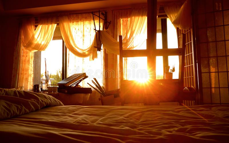View of Sun Rising Through An Artist's Bedroom Studio Window. View of the sun rising into an artist`s bedroom studio  and filling the window with golden morning royalty free stock image