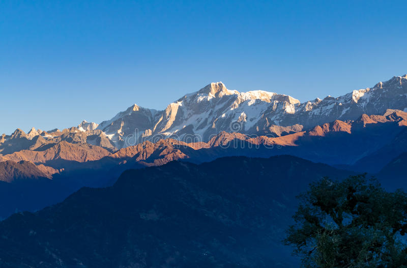 View of sunrise in Garhwal himalayas of uttrakhand from Deoria Tal camping site. Golden sun rays falling on snow cladded Kedarnath peak and other peaks of royalty free stock image