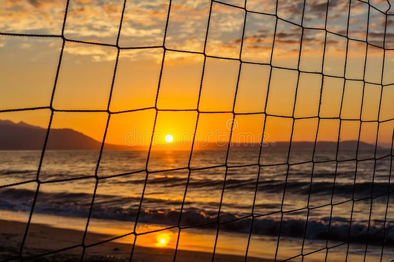 View of the sunrise through the volleyball net. royalty free stock photos