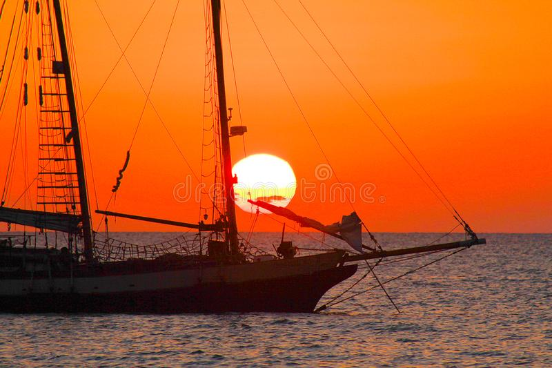 View on sunset from caribbean beach with orange red glowing sky and black silhouette of isolated sailing boat. Jamaica stock photography