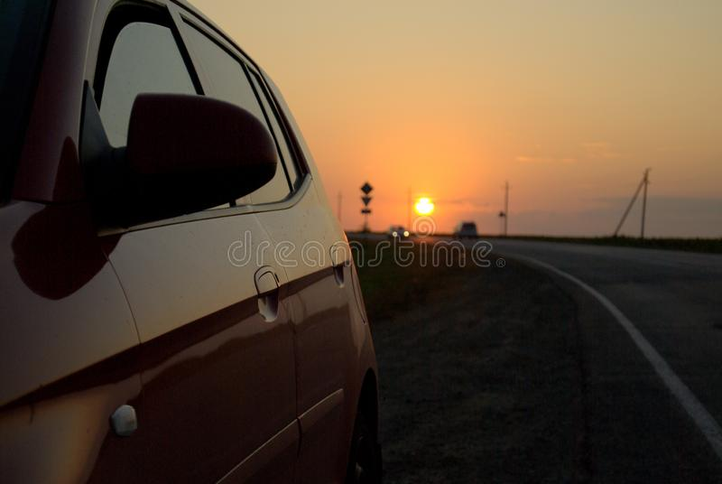 View of the sunset, country road and reflection of sunset on the side surface of a passenger car. The shot was taken in Russia. View of the sunset, country road royalty free stock image