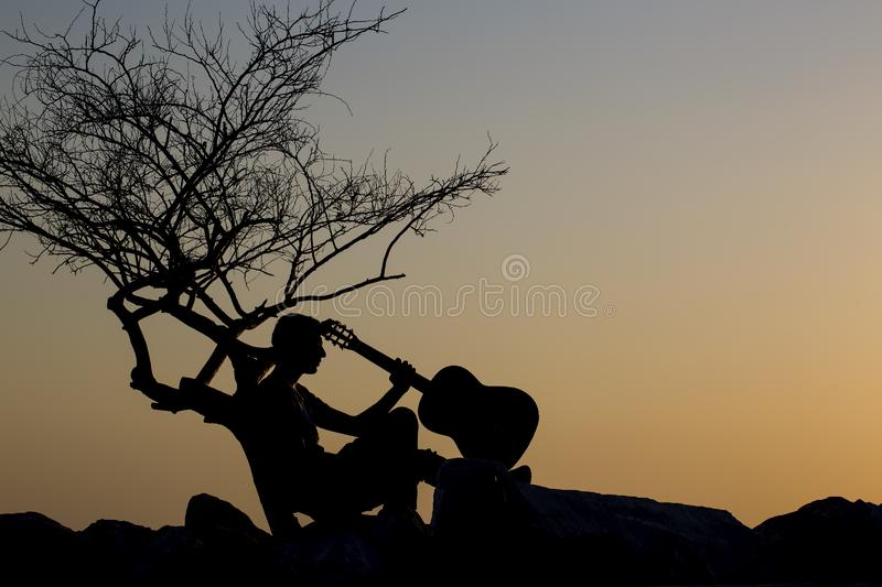View of the sunset; young man with guitar royalty free stock image